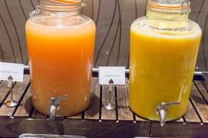 Grapefruitsaft und Orangensaft in großen Glasbehältern