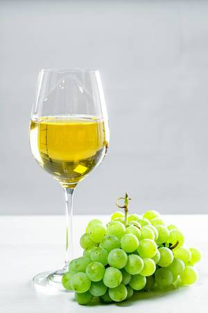 Grapes and white wine glass on a wooden table, front view (Flip 2019)