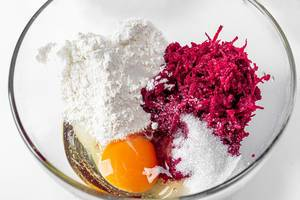 Grated beetroot, flour, sugar, soda and egg in a glass bowl close-up (Flip 2019)