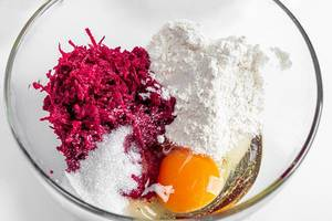 Grated beetroot, flour, sugar, soda and egg in a glass bowl close-up