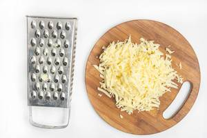Grated yellow cheese on the wooden board