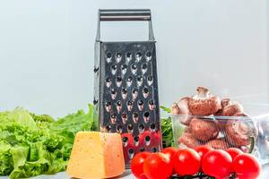 Grater with cheese and fresh vegetables on the kitchen table (Flip 2019)