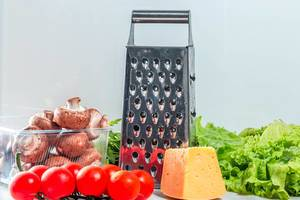 Grater with cheese and fresh vegetables on the kitchen table