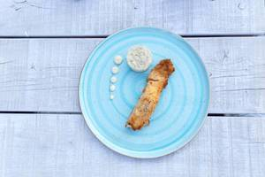 Gratinated salmon with parmesan crust, dark rice and wasabi mayonnaise in a light blue plate