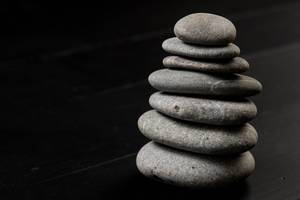 Gray Balanced Stones auf dem schwarzen Hintergrund