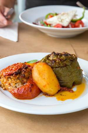 "Greek dish called ""Gemista"", with red and green stuffed peppers, rice, pine nuts, raisins, mint leaves, fruits and yellow sauce"
