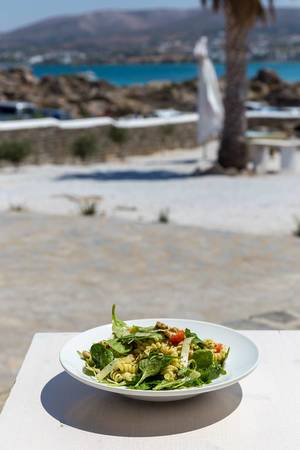 Greek noodle dish with green leaves, tomatoes and parmesan cheese on an outside table near the beach