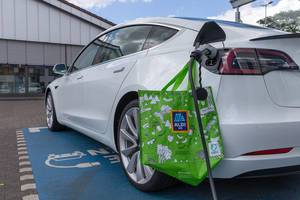 Green Aldi South shopping bag next to the Phoenix Conact Type 2 charging plug at the charging station for electric cars