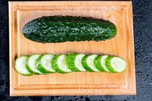Green cucumber on kitchen Board