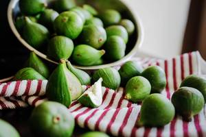 Green figs coming out of a metal bowl to a kitchen cloth