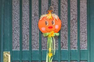 Green wooden door with handmade Halloween decoration