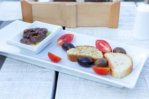 Griechische Vorspeise: schwarze Oliven, Cherrytomaten und fein gehackte Oliven in Olivenöl