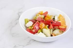 Griechischer Salat in einer weißen Schale auf einer Marmoroberfläche