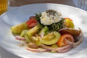 Griechischer Salat mit Kräutern, Zwiebeln, roten und gelben Tomaten, in einem Restaurant auf Paros