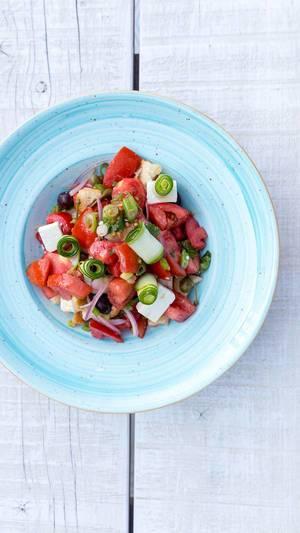 Griechischer Salat mit Tomate, Gurke, Zwiebel, sonnengetrocknete Tomate, Fetakäse, Kapern und Olivenöl. Draufsicht