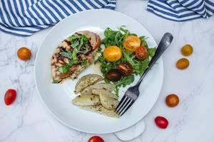 Griechisches Hühnerfleisch, mit Käse und getrockneten Tomaten gefüllt, neben Tomaten und einem grünen Salat