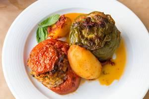 """Griechisches Mittagessen """"Gemista"""": bunte, gefüllte Paprika und Tomaten, Reis, Minze, Pinienkerne und Rosinen"""