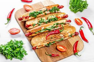Grilled hot dogs with fresh vegetables, herbs and chili peppers