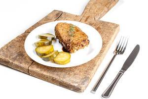 Grilled kebab with pickled cucumber on the kitchen board with knife and fork