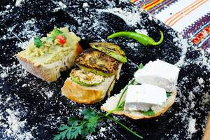 Grilled zucchini slices, eggplant salad and cheese sandwiches on black background (Flip 2019)