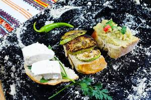 Grilled zucchini slices, eggplant salad and cheese sandwiches on black background