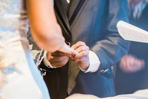 Groom inserting a ring to the Bride