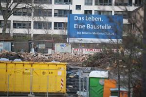 """Große Baustelle vor einem Gebäude mit dem Schild """"Das Leben. Eine Baustelle. Die Bibel in Matthäus 7,24.25"""""""