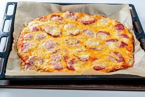 Große frische Pizza mit geräuchertem Wurst und Mozzarellakäse auf schwarzem Backblech