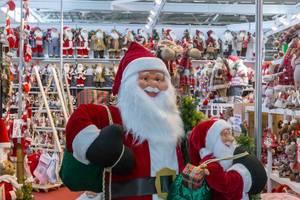 Große fröhliche Weihnachtsmann Figur umgeben von verschiedenen kleineren Variationen im Hintergrund