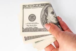 Große Geldscheine in einer Frauenhand vor weißem Hintergrund
