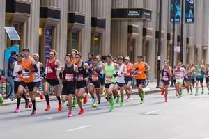 Große Gruppe von männlichen Athleten in bunten Laufschuhen laufen vor dem Central Standard Building während des Chicago Marathons am 13.10.2019