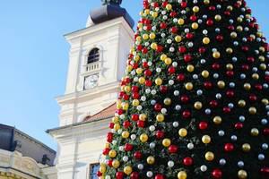 Großer Weihnachtsbaum mit roter, weißer und goldener Deko auf einem Platz an einem sonnigen Tag