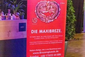 Großes rotes Schild mit Werbung für die Maxibreze bei der Bits & Pretzels Konferenz in München