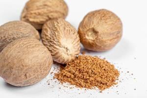 Ground nutmeg and whole on white background, close up