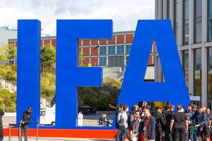 Group of people gathers in front of the blue IFA logo for the exhibition in Berlin