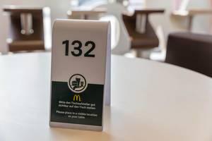 Grün-weißer Tischaufsteller mit Mc Donalds Logo hilft dem Servicepersonal die Bestellung am Tisch zu srevieren