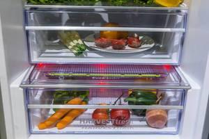Grundig fridge with illuminated HarvestFresh drawer, filled with fruits and vegetables