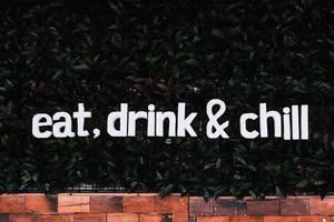 """Grüne bepflanzte Wand mit den Worten """"Eat, drink and chill""""  - essen, trinken und entspann"""
