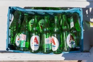 Grüne, griechische Bierflaschen in einem Plastikkorb