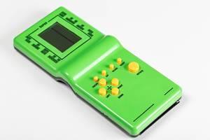 Grüne Handheld-Konsole: Elektronisches Tetrisspiel vor weißem Hintergrund