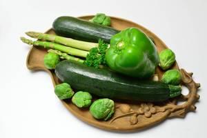 Grüne Paprika mit Zucchini, grünem Spargel, Rosenkohl und Petersilie auf Tonteller
