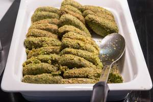 Grüne Veggie Taler als Fleischersatz, in einem weißen Behälter mit einem Löffel, am Hotelbüfett