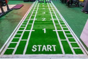 Grüner Fitness-Teppich mit Start-Zeichen und Zahlen in einem Probe-Fitnessraum auf dem Fibo-Messe Köln