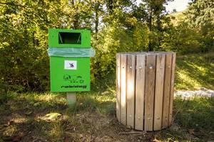 Grüner Hundeabfallcontainer neben Abfallcontainer im Park