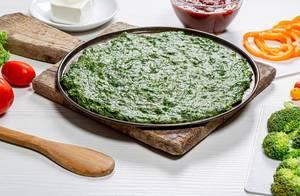 Grüner Pizzaboden und frisches Gemüse auf einem weißen Holztisch