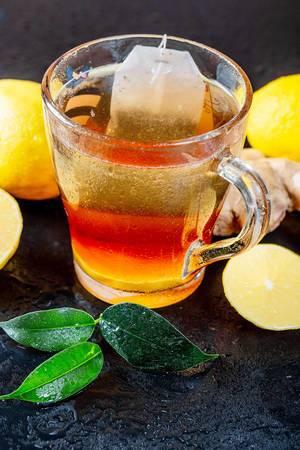 Grüner Tee mit Zitronensaft und Ingwer in einer Tasse aus Glas auf schwarzem Hintergrund