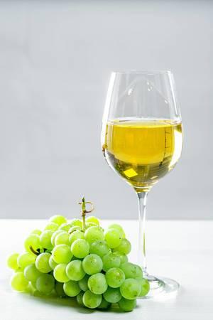 Grüner Weintraubenstrang neben einem Glas Weißwein, auf einem hellen Tisch