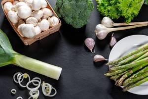 Grünes, frisches Gemüse und Pilze vor schwarzem Hintergrund
