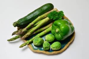 Grünes Gemüse - Grüne Paprika mit Rosenkohl, grünem Spargel, Zucchini un Petersilie auf blauem Tonteller