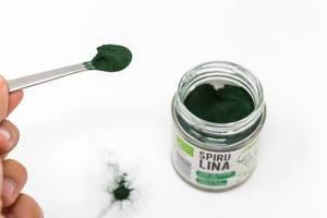Grünes Spirulinapulver auf einem Löffel, neben dem Verpackungsglas auf einem weißen Tisch